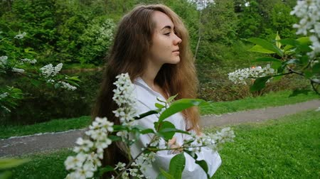 ninfa : Pretty European girl model posing on camera in blossoming bird cherry. Young woman with long fluffy hair and a branch on her head is photographed in the park, slow motion