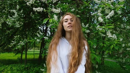 juba : Portrait of a European girl with long flowing hair in nature, slow motion. Beautiful cute young woman posing and looking at the camera on a background of cherry blossoms in summer Stock Footage