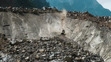 landslide : Slow motion rockfall close up. Big stones falling down from a melting glacier in the background of rocky mountains Stock Footage