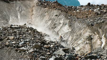 landslide : Slow motion rockfall in the mountains close up. People run away from falling rocks in the mountains, crash and fear. Instinct of self-preservation in an emergency situation