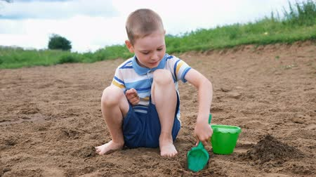 çukur : Little boy is playing digging a pit with a shovel. Kid playing on the beach Stok Video