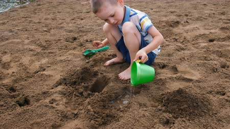coletando : Little boy pours water from a bucket into a hole in the sand. Kids playing on the beach