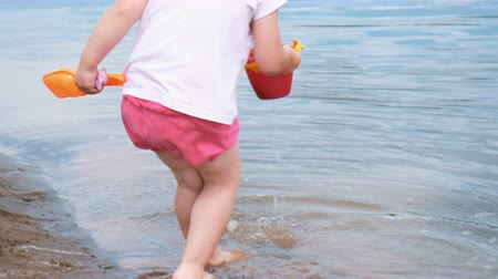 coletando : Little girl picks up and pours water out of the bucket into the sand closeup. Child playing on the beach.