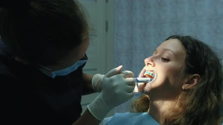 fixação : Orthodontist applies the gel on the teeth before installing the bracket system. Visit to the dentist