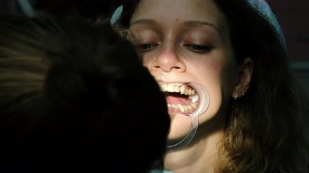fixação : Woman is treating teeth with an orthodontic fixator in her mouth close up. Visit to the dentist