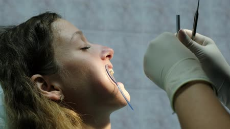 düzeltme : Visit to the dentist. Orthodontist doctor sets up iron braces for a young woman close up