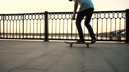 bruslař : Man on a skateboard performs an ollie flip - trick kickflip leap on a board at sunset, slow motion Dostupné videozáznamy
