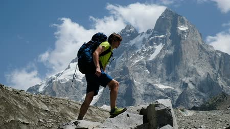 alpinista : Man with a backpack tourist climbs on a rock and raises his hands up in the mountains mountains in the campaign. The concept of victory and success, achieving the goal, slow motion
