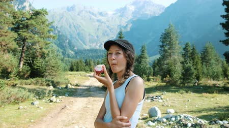 mastigação : Portrait of a beautiful young woman tourist eating an apple in a hike in the mountains. European girl snacks with fruit on a nature trip Stock Footage