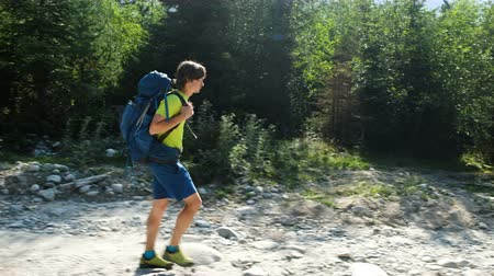 hiking : Young man tourist in trekking boots with a backpack walking in a hike against a beautiful mountain landscape, camera movement Stock Footage