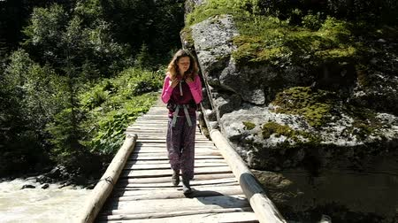 cruzes : Woman tourist with a backpack walks along a wooden bridge across a fast mountain stream, slow motion Vídeos