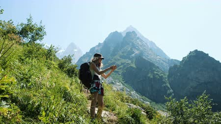 альпинизм : Woman climber hiker tourist with a backpack in the hike doing selfie and takes pictures of the landscape on the phone against the backdrop of beautiful mountains