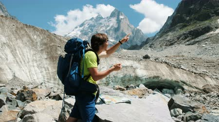 rota : Tourist man with a backpack exploring the route on the map and phone GPS, adds a map and goes on a route in the mountain hike Stok Video