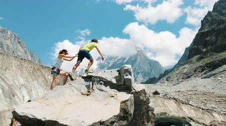 reaching : Family couple of tourists in the mountain trek climb to the top of the stone and raise their hands up, kiss and enjoy the climb. The concept of love, success and goal achievement