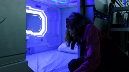 foglalás : Woman looks with surprise at the Sleepbox with neon lights, the space capsule container for sleeping at the airport Stock mozgókép
