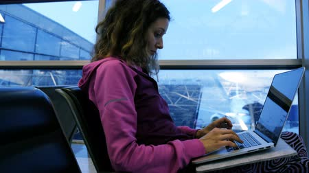 yazışma : Woman tourist freelancer typing on laptop, waiting for plane and flight at airport in waiting room Stok Video
