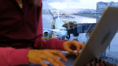 vzdálený : Woman hands is typing on a laptop by the window at an airport on the background of an airplane close-up Dostupné videozáznamy