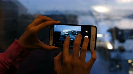 várjon : Woman at the airport takes a picture of a plane through a glass on a smartphone close-up