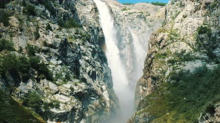 kaukázus : Huge waterfall in the mountains, a powerful stream of water falls from the cliff. Stock mozgókép
