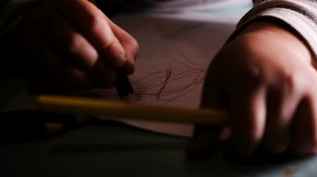 estudioso : Small child learns to draw with pencils on paper, slow motion