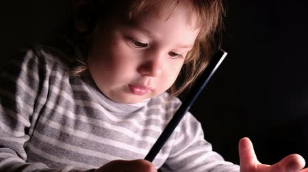 estudioso : Little girl child learns to draw with a pencil on paper, slow motion