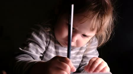 estudioso : Little girl diligently draws a pencil on a piece of paper, slow motion Stock Footage