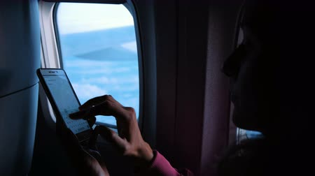 correspondência : Woman using smartphone and dials a message on the phone on the airplane against the window in flight in the evening. Fingers touch the screen. Stock Footage