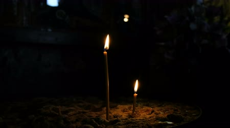 church utensils : Two wax candles stand in the sand in the Orthodox ancient dark temple
