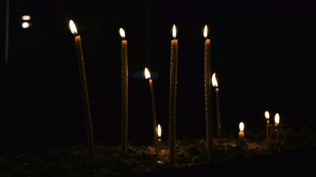 ortodoxia : Wax candles burn and stand in the sand in the Orthodox Church of the ancient temple