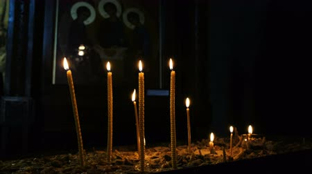 church utensils : Wax candles burn and stand in the sand in the Orthodox Church of the ancient temple on the background of the icon of the Holy Trinity
