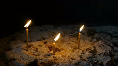 church utensils : Wax candles burn and stand in the sand in the Orthodox ancient temple