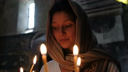repentance : Woman in a headscarf puts a candle and prays before the icon in the Orthodox Catholic Church