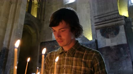 repentance : Believing man puts a candle and prays before an icon in the Orthodox Catholic Church Stock Footage