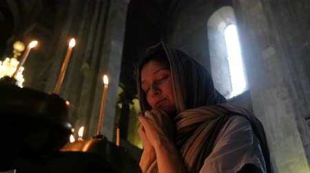 repentance : Woman in a headscarf praying before an icon in the Orthodox Catholic Church Stock Footage