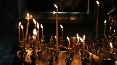 church utensils : Wax candles burn and stand on the sand in the censer of the Orthodox ancient temple, slow motion Stock Footage