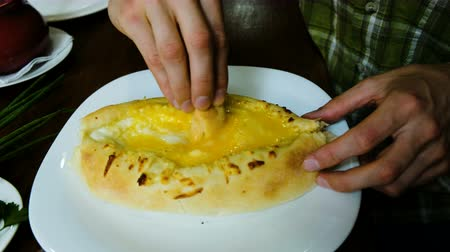 gürcü : Man is eating a national Georgian dish - khachapuri. The guy breaks off a piece of bread and dipping it in a filling of cheese and butter close-up.