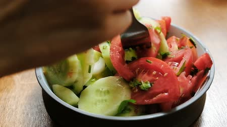 villa : Woman eats a salad of fresh vegetables cucumbers and tomatoes on a fork, concept of proper nutrition, healthy vegetarian food close-up. Slow motion Stock mozgókép