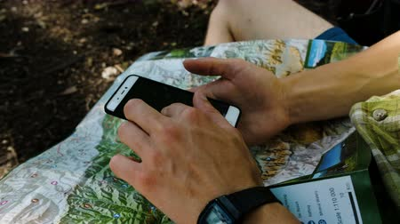compares : Man tourist sits in the forest checks the route on a paper map and phone using GPS on a smartphone. Touches the screen close-up