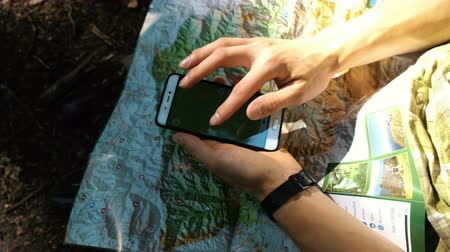 compares : Man tourist sits in the forest and uses an electronic map on the phone, checks the route on a paper map using GPS on a smartphone. Touches the screen close-up