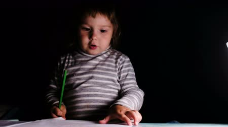 highlights : Baby girl draws with a pencil and shows a drawing, closeup Stock Footage