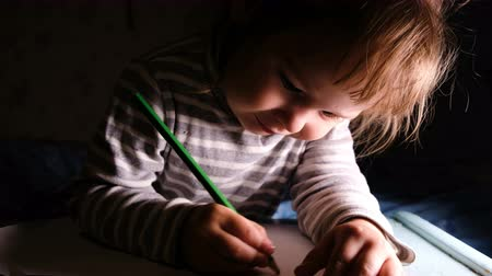 estudioso : Little girl draws green pencil on a sheet of paper close-up