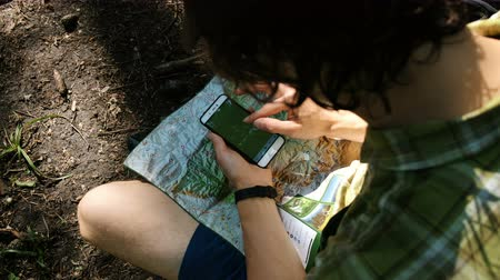 compares : Tourist sits on the ground in the forest and uses an electronic map on the phone, checks the route and looks at the path using GPS on the smartphone.