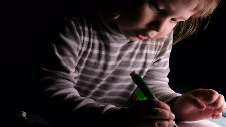 small pen : Little girl child learns to draw with markers and pencils at home on a piece of paper in the dark. Stock Footage