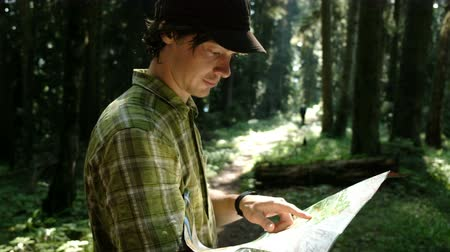 compares : Man tourist standing in the forest and checks the route on a paper map and looks at the path