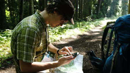 compares : Tired tourist with a backpack sits in the forest and uses an electronic map on his phone, checks the route on a paper map and looks at the path using GPS on a smartphone.