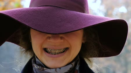 brackets : Portrait of a girl in a hat smiling with braces on her teeth, orthodontic smile, crooked teeth