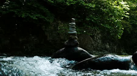 formado : Tower or cairn stands on a cobblestone in a mountain river, slow motion