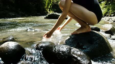 que vale a pena : Young woman in a swimsuit sits on a stone and splashing water in a mountain cold river