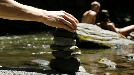 formado : Man puts a cairn standing on a cobblestone in a mountain river against the background of tourists. Vídeos