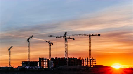 andaime : Construction cranes working at sunset, workers engaged in construction, time lapse